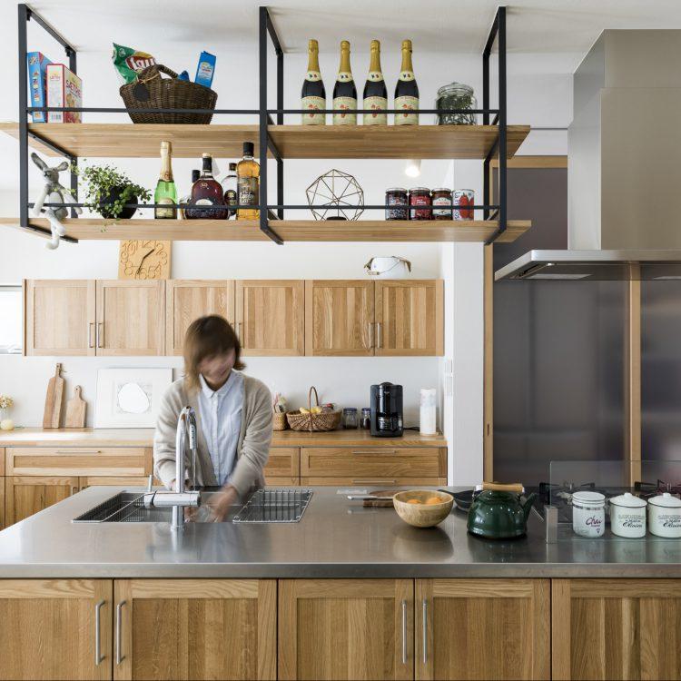 岐阜県瑞穂市の二世帯住宅リノベーション事例のアイランドキッチンで家事をするママ